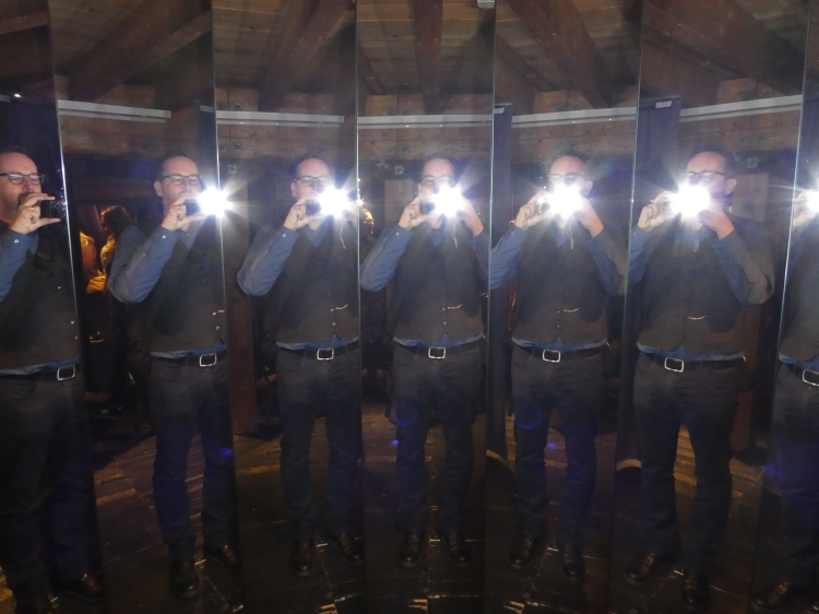 Multiple images of a man taking a photograph in a set of mirrors